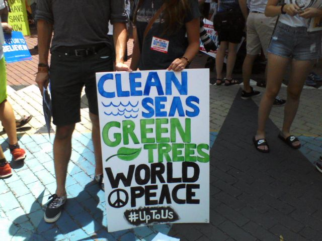 "Handmade sign: ""Clean Seas"" in blue with blue waves, ""Green Trees"" in green with a green leaf, ""World Peace"" with a peace symbol in black and hashtag ""#UpToUs""."