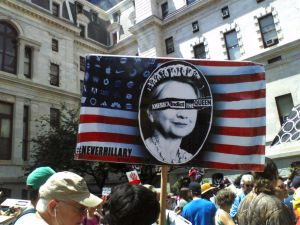 "Crowd of protesters outside a large white building. Most prominent is a sign — the American flag is in the background except the stars have been replaced with corporate logos. In the center of the flag is an oval similar to the oval on currency with a photo of Hillary Clinton, crowned, with the words ""America Indict The Queen"" across her eyes. Hashtag #NEVERHILLARY in the bottom left of the sign."