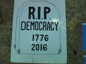 "White homemade sign of a gravestone that says ""R.I.P. DEMOCRACY 1776 2016"" in black letters."
