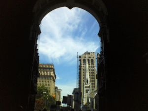 View of the sky and buildings through an archway.